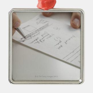 Closeup of hands signing prescription metal ornament