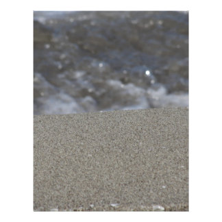Closeup of sand beach with sea blurred background letterhead