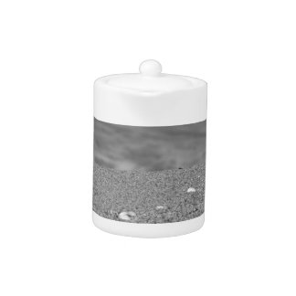 Closeup of sand beach with sea blurred background teapot
