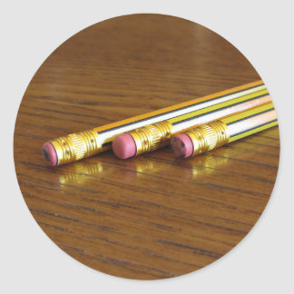 Closeup of used pencil erasers on wooden table classic round sticker