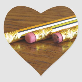 Closeup of used pencil erasers on wooden table heart sticker