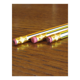 Closeup of used pencil erasers on wooden table letterhead