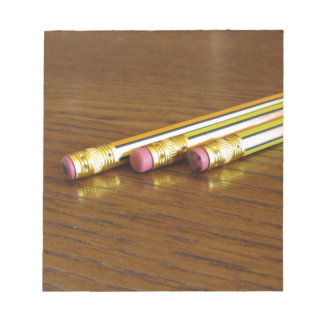 Closeup of used pencil erasers on wooden table notepad