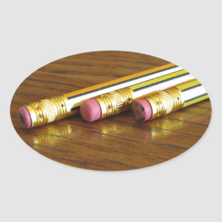 Closeup of used pencil erasers on wooden table oval sticker