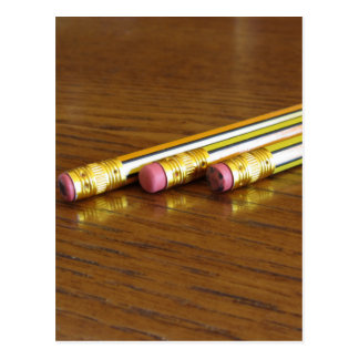 Closeup of used pencil erasers on wooden table postcard