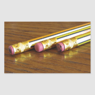 Closeup of used pencil erasers on wooden table rectangular sticker