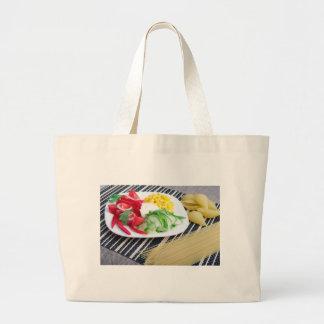 Closeup view of a vegetarian dish of raw vegetable large tote bag