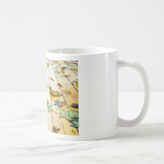 Closeup view on a wet green and yellow leaves coffee mug