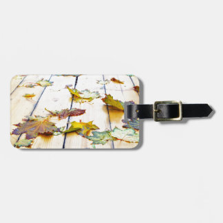 Closeup view on a wet green and yellow leaves luggage tag
