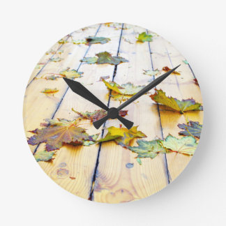 Closeup view on a wet green and yellow leaves round wallclock