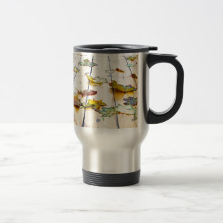 Closeup view on a wet green and yellow leaves travel mug