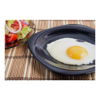 Closeup view on fried eggs with yolk on a plate poster