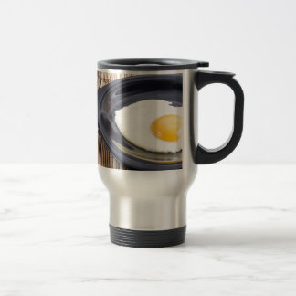 Closeup view on fried eggs with yolk on a plate travel mug