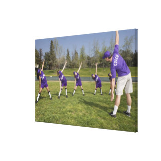 Coach and little league players stretching canvas print