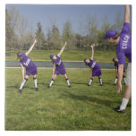 Coach and little league players stretching large square tile