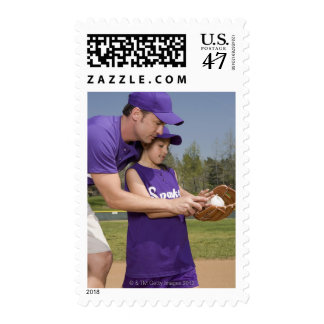 Coach teaching little league player postage