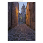 Cobbled alleyway of old city lit up at night card
