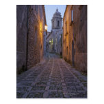 Cobbled alleyway of old city lit up at night postcard