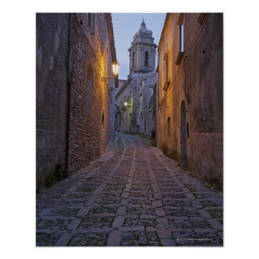 Cobbled alleyway of old city lit up at night poster