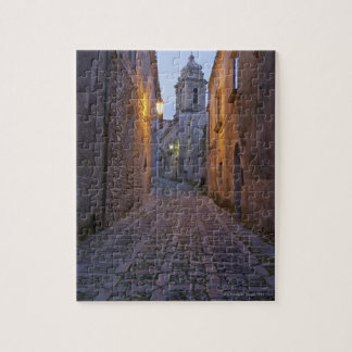 Cobbled alleyway of old city lit up at night puzzles