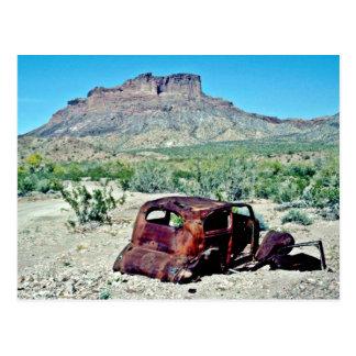 Coche antiguo aherrumbrado delante de la mota postal