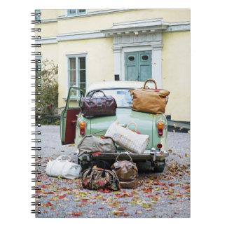 Coche del vintage con las porciones de equipaje libreta espiral