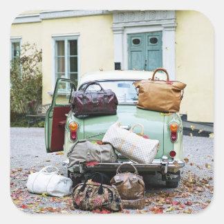 Coche del vintage con las porciones de equipaje pegatina cuadrada