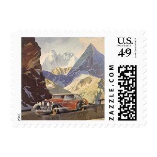 Coche del vintage en el camino de la montaña con timbre postal