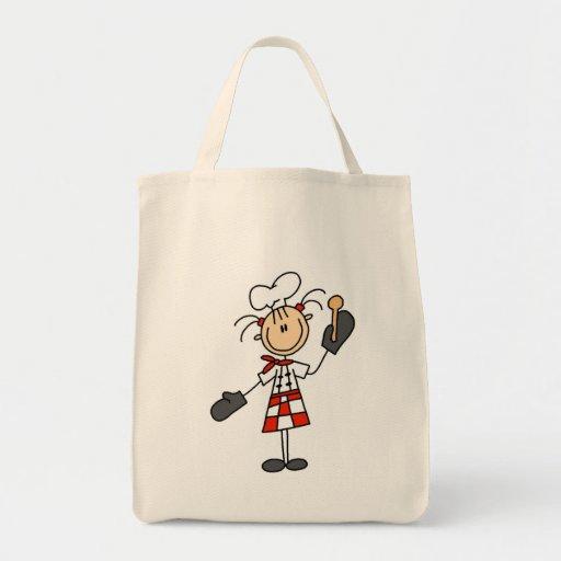 Cocinero de sexo femenino con las camisetas y los  bolsa lienzo