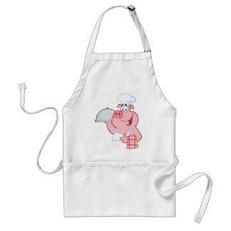 Cocinero feliz del cerdo que lleva a cabo una mues delantal