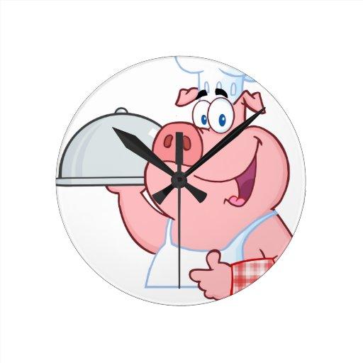 Cocinero feliz del cerdo que lleva a cabo una mues relojes de pared