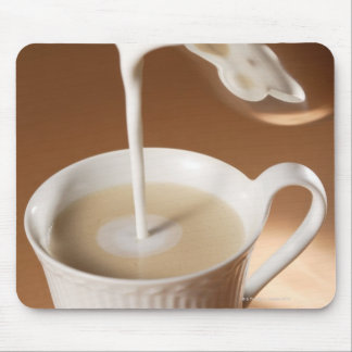 Coffee with milk being poured in mouse pad