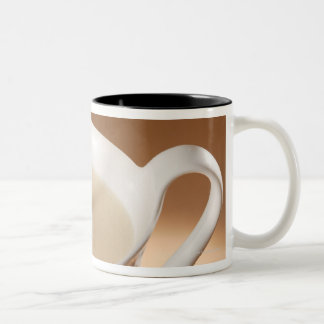 Coffee with milk being poured in mug