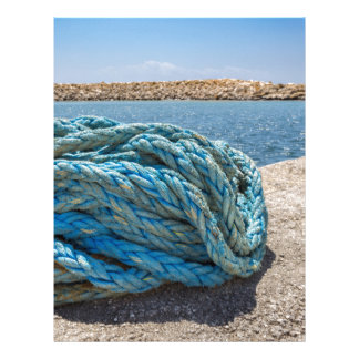 Coiled blue mooring rope at water in greek cave letterhead