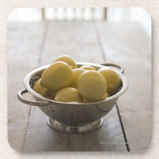 Colander with lemons on wooden table beverage coaster