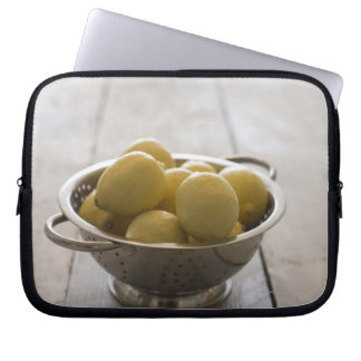 Colander with lemons on wooden table computer sleeve