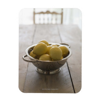 Colander with lemons on wooden table magnet