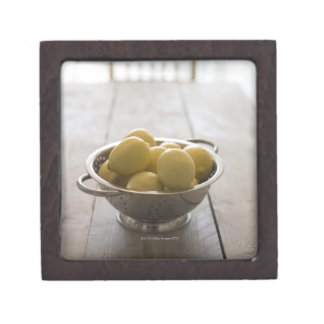 Colander with lemons on wooden table premium gift boxes