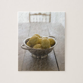 Colander with lemons on wooden table jigsaw puzzles