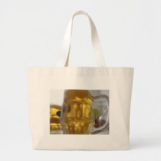 Cold mug of light beer on the table at a restauran large tote bag
