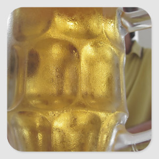 Cold mug of light beer on the table at a restauran square sticker