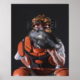 Colector del béisbol que sostiene la bola en mitón poster