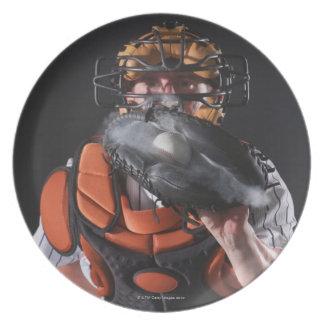 Colector del béisbol que sostiene la bola en mitón