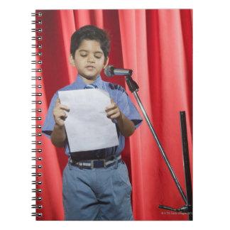Colegial pronunciar discurso en una etapa libros de apuntes con espiral