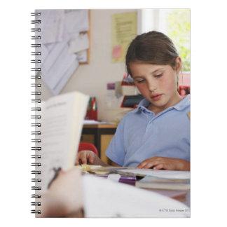 colegiala que concentra en la lectura en clase libro de apuntes con espiral