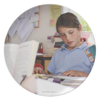 colegiala que concentra en la lectura en clase plato de comida