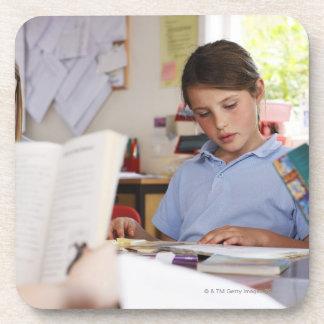 colegiala que concentra en la lectura en clase posavaso