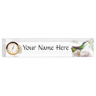 Colibrí y placa de identificación de las flores