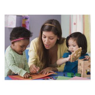 Color de ayuda de los niños del profesor en la tarjeta postal