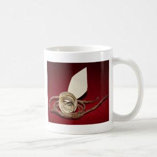 Color de rosa de papel con guita en fondo rojo taza
